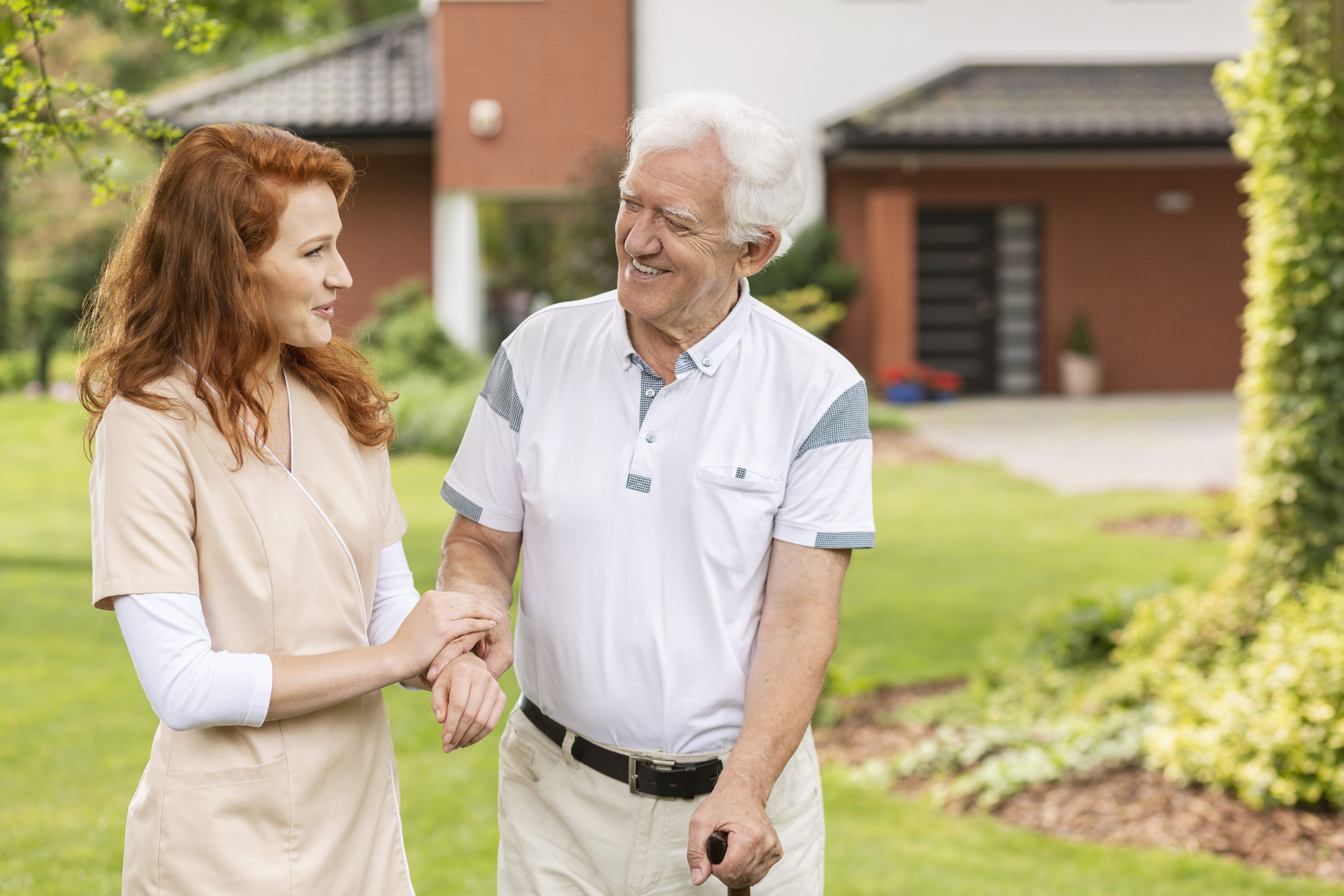 Smiling grey-haired senior man with a walking stick talking to a helpful caretaker in uniform in the garden of a nursing home.